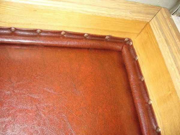 Проем по периметру также можно окантовать валиком из кожзама